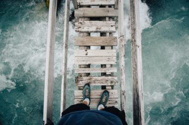 person on a bridge over rushing river